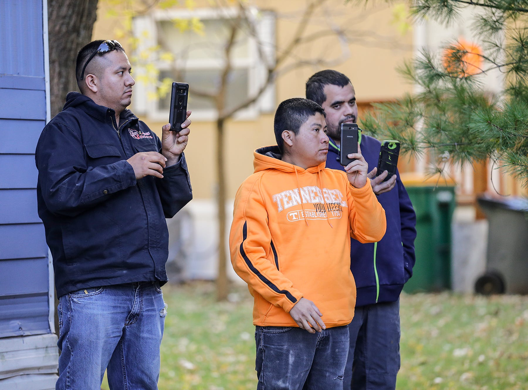 Bystanders film a mobile home fire Tuesday, October 23, 2018 at 21 Gaslight Drive in the Gaslight Terrace mobile home park in North Fond du Lac, Wisconsin. Fire departments from multiple agencies were on hand to battle the fire. Doug Raflik/USA TODAY NETWORK-Wisconsin
