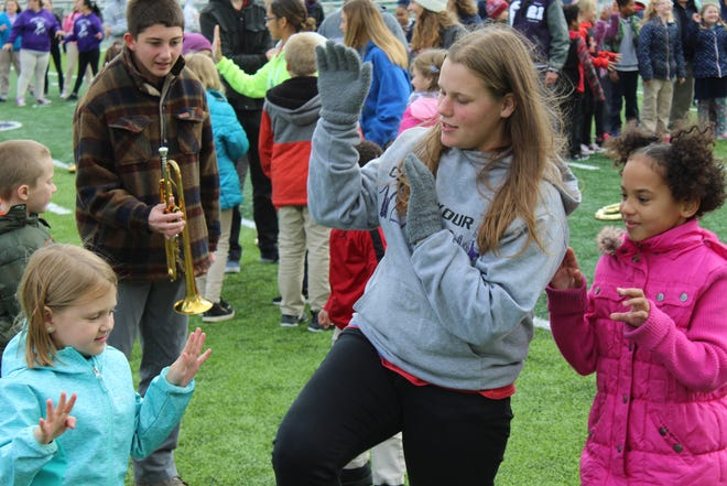 "Kendra Smith, center, a sophomore that performs with the Fremont Ross Marching Little Giants, shows Stamm Elementary School students how to do the Michael Jackson ""Thriller"" dance Wednesday at Don Paul Stadium."
