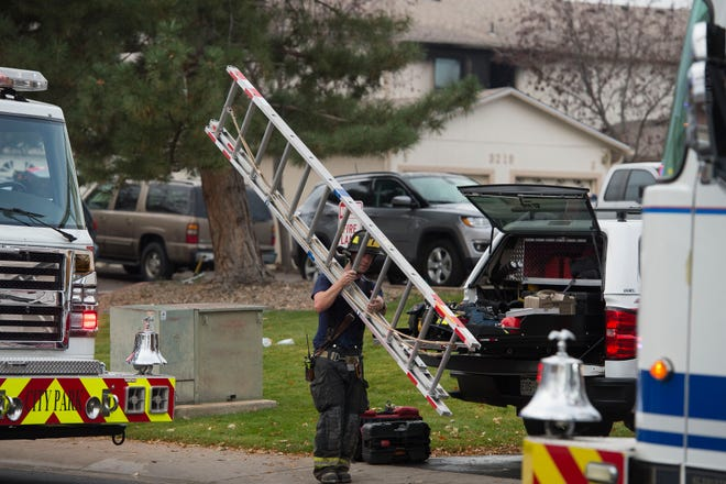A firefighter carries a ladder back from an early-morning house fire on Wednesday morning, Oct. 24, 2018, on the 3200 block of Sumac Street in Fort Collins, Colo. There is one confirmed fatality from the fire and Poudre Fire Authority and the Fort Collins Police Services are currently conducting an investigation.