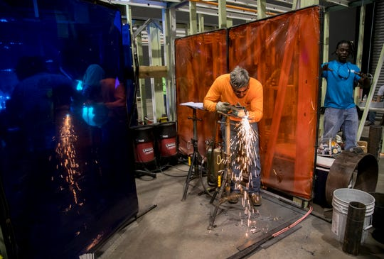 Fabian Rodriguez, center, cuts names out of metal as another welder demonstrates his craft for high school students at the Build My Future Lee County event at the Lee Civic Center on Wednesday, Oct. 24, 2018.