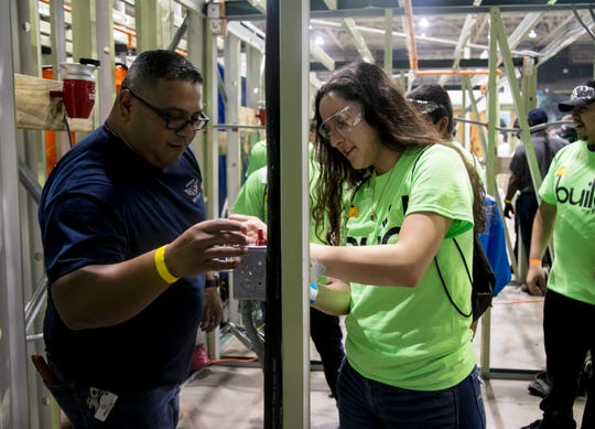 Juan Silva, of American Electrical, helps South Fort Myers High School student Bethany Fuentes wire an electrical outlet box at the the Build My Future Lee County event at the Lee Civic Center on Wednesday, Oct. 24, 2018.