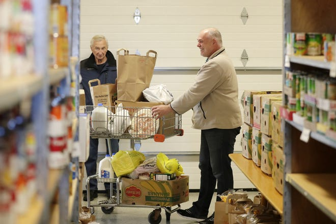 Director Scott Behling loads up a cart of food during distribution at the De Pere Christian Outreach Food Pantry on Wednesday.