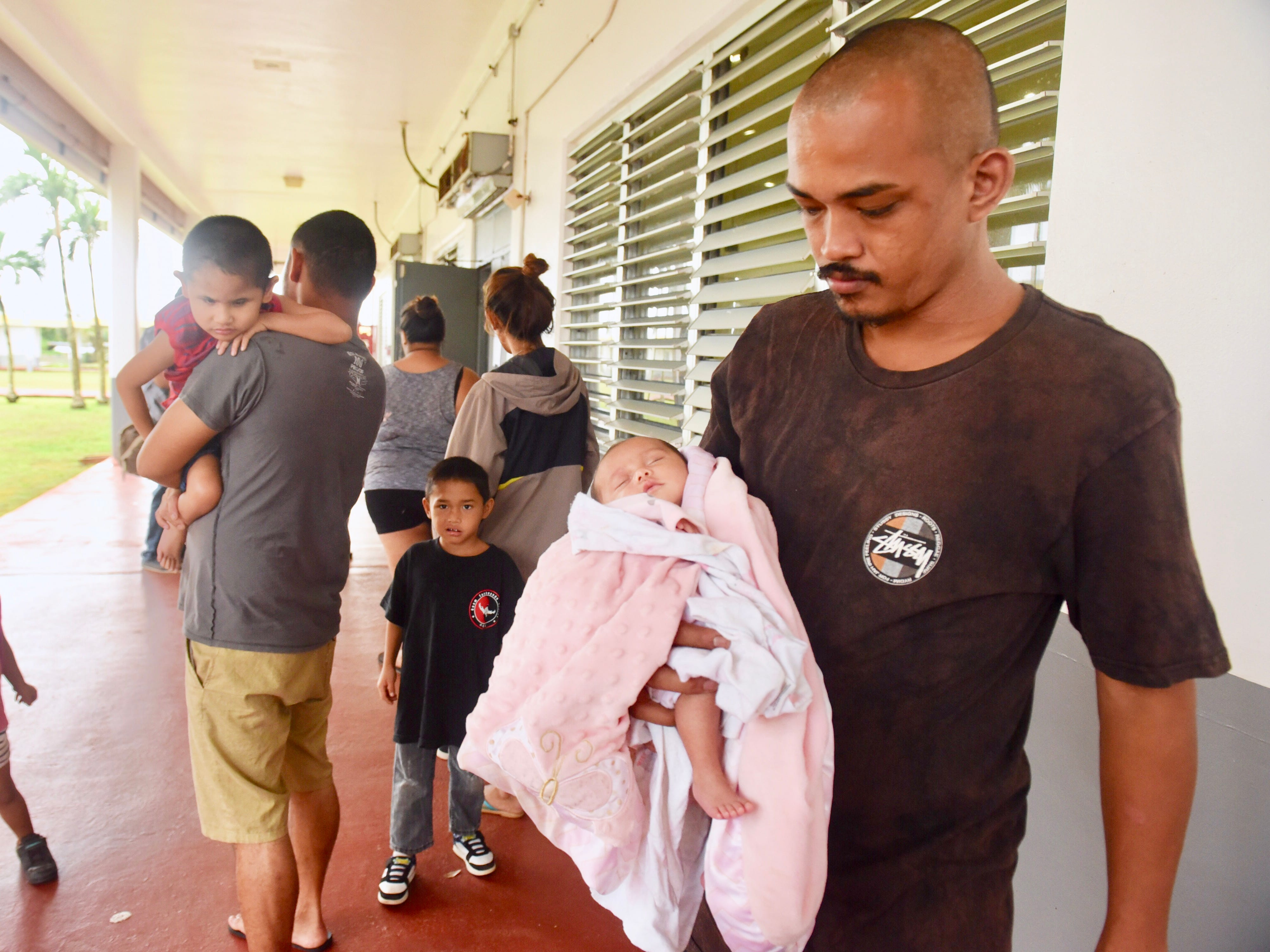 Jarrett Pangelinan Cruz carries his 1-month-old niece, Jayvery Pangelinan, as he gathers with family members in the hallway of Astumbo Elementary School in Dededo, where they were seeking shelter from Super Typhoon Yutu on Wednesday, Oct. 24, 2018. Eight public schools were opened as shelters at 2 p.m. Wednesday, two hours after Condition of Readiness 2 was declared for the typhoon.