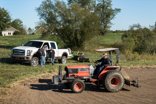 Ryan Doane, front, works on seeding the hole three green as his co-workers Kevin Doane, back left, and Jimmy Elrod, back right, talk about which hole they need to seed next at the site of the old Players Club Golf Course in Henderson, Ky., Thursday, Oct. 18. The Henderson City Commission unanimously voted to approve a contract with K&J Course Management, Tuesday evening, Oct. 23, to rehabilitate and reopen the golf course by July 1, 2019.
