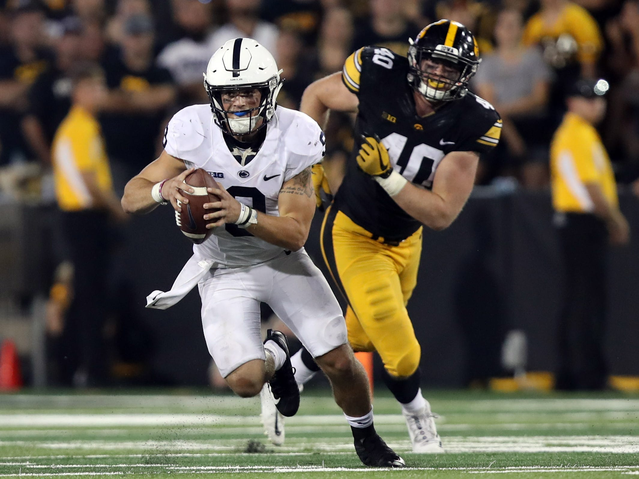 Penn State quarterback Trace McSorley (9) has given Parker Hesse (40) and Iowa fits over the past two seasons. It'll be up to the defensive ends to keep him contained Saturday at Beaver Stadium.