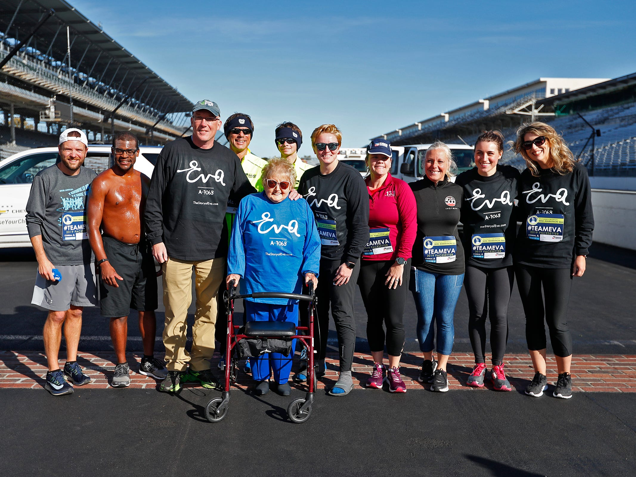 Holocaust survivor Eva Kor, center, joins others at the Indianapolis Motor Speedway Yard of Bricks for photos, Wednesday, Oct. 24, 2018, during the pace-setting run for the 2019 OneAmerica 500 Festival Mini-Marathon.  The 500 Festival will donate $1 to the CANDLES Holocaust Museum in Terre Haute for every mini-marathon participant who finishes the 2019 race in a better time than Team Eva.  Kor ran the very last of the relay race.