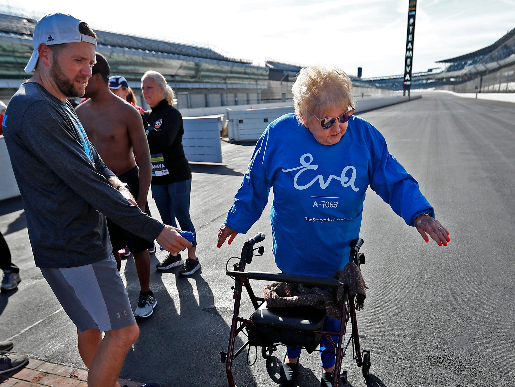 Holocaust survivor Eva Kor, rignt, and runner Brad Chaney, look at the Indianapolis Motor Speedway Yard of Bricks, Wednesday, Oct. 24, 2018, during the pace-setting run for the 2019 OneAmerica 500 Festival Mini-Marathon.  The 500 Festival will donate $1 to the CANDLES Holocaust Museum in Terre Haute for every mini-marathon participant who finishes the 2019 race in a better time than Team Eva.  Kor ran the very last of the relay race.