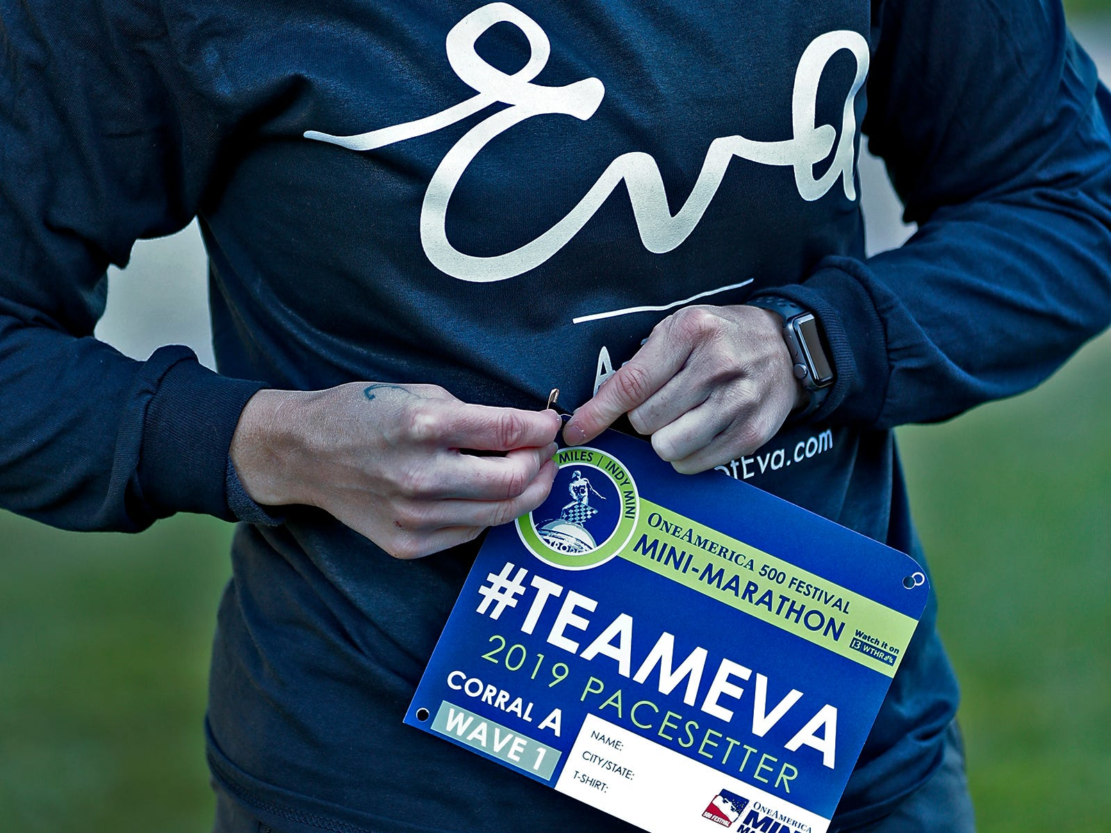 Mika Brown puts on her Team Eva bib to run the first leg, Wednesday, Oct. 24, 2018, of the pace-setting run for the 2019 OneAmerica 500 Festival Mini-Marathon.  The 500 Festival will donate $1 to the CANDLES Holocaust Museum in Terre Haute for every mini-marathon participant who finishes the 2019 race in a better time than Team Eva.  Holocaust survivor Eva Kor joined the fun at the Indianapolis Motor Speedway's Yard of Bricks and ran the very last part of the race.