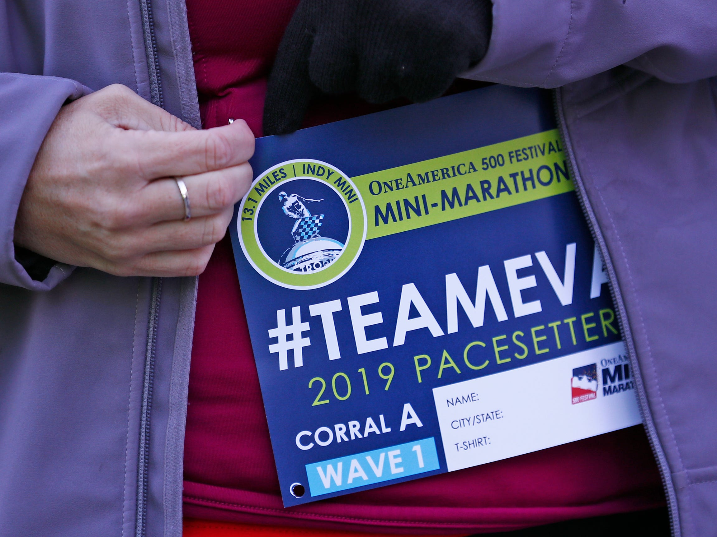 Runners put on Team Eva race bibs before starting the pace-setting run for the 2019 OneAmerica 500 Festival Mini-Marathon, Wednesday, Oct. 24, 2018. The 500 Festival will donate $1 to the CANDLES Holocaust Museum in Terre Haute for every mini-marathon participant who finishes the 2019 race in a better time than Team Eva.  Holocaust survivor Eva Kor joined the fun at the Indianapolis Motor Speedway's Yard of Bricks and ran the very last part of the race.