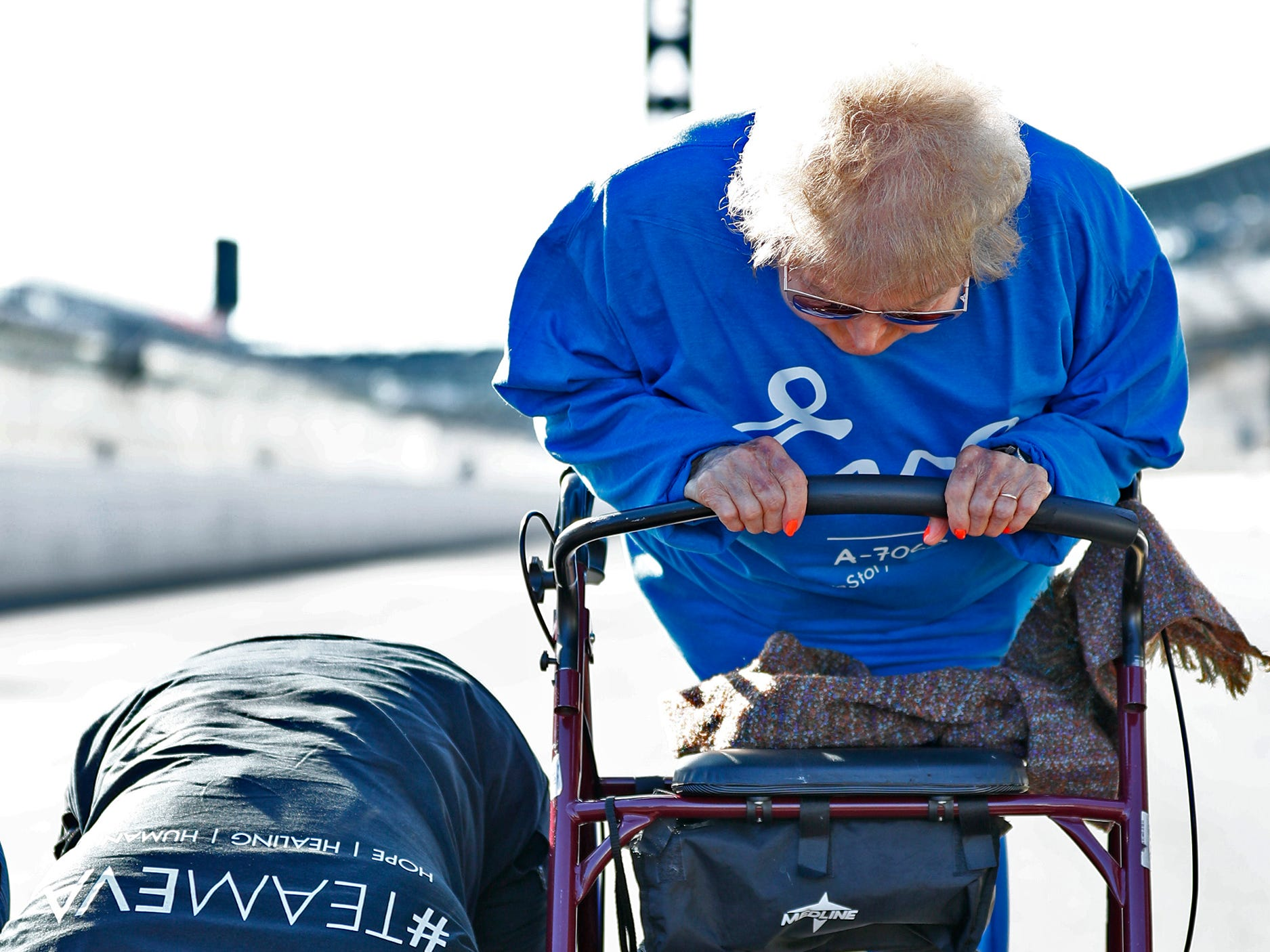 """Holocaust survivor Eva Kor, right, joins others """"kissing the bricks,"""" at the Indianapolis Motor Speedway Yard of Bricks, Wednesday, Oct. 24, 2018, midway during the pace-setting run for the 2019 OneAmerica 500 Festival Mini-Marathon.  The 500 Festival will donate $1 to the CANDLES Holocaust Museum in Terre Haute for every mini-marathon participant who finishes the 2019 race in a better time than Team Eva.  Kor ran the very last of the relay race."""