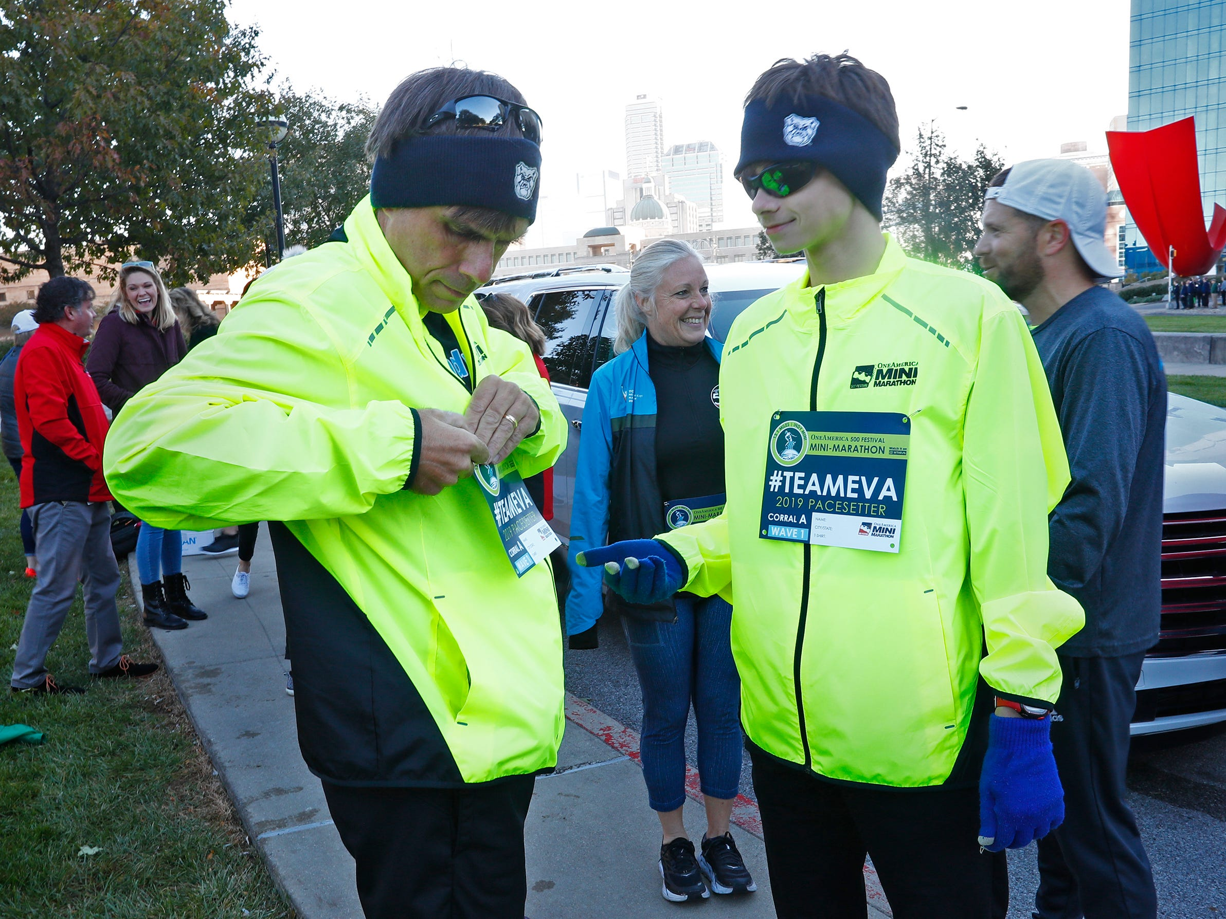 Rob and Ryan Rueff put on their Team Eva race bibs, Wednesday, Oct. 24, 2018, before the pace-setting run for the 2019 OneAmerica 500 Festival Mini-Marathon.  The 500 Festival will donate $1 to the CANDLES Holocaust Museum in Terre Haute for every mini-marathon participant who finishes the 2019 race in a better time than Team Eva.  Holocaust survivor Eva Kor joined the fun at the Indianapolis Motor Speedway's Yard of Bricks and ran the very last part of the race.