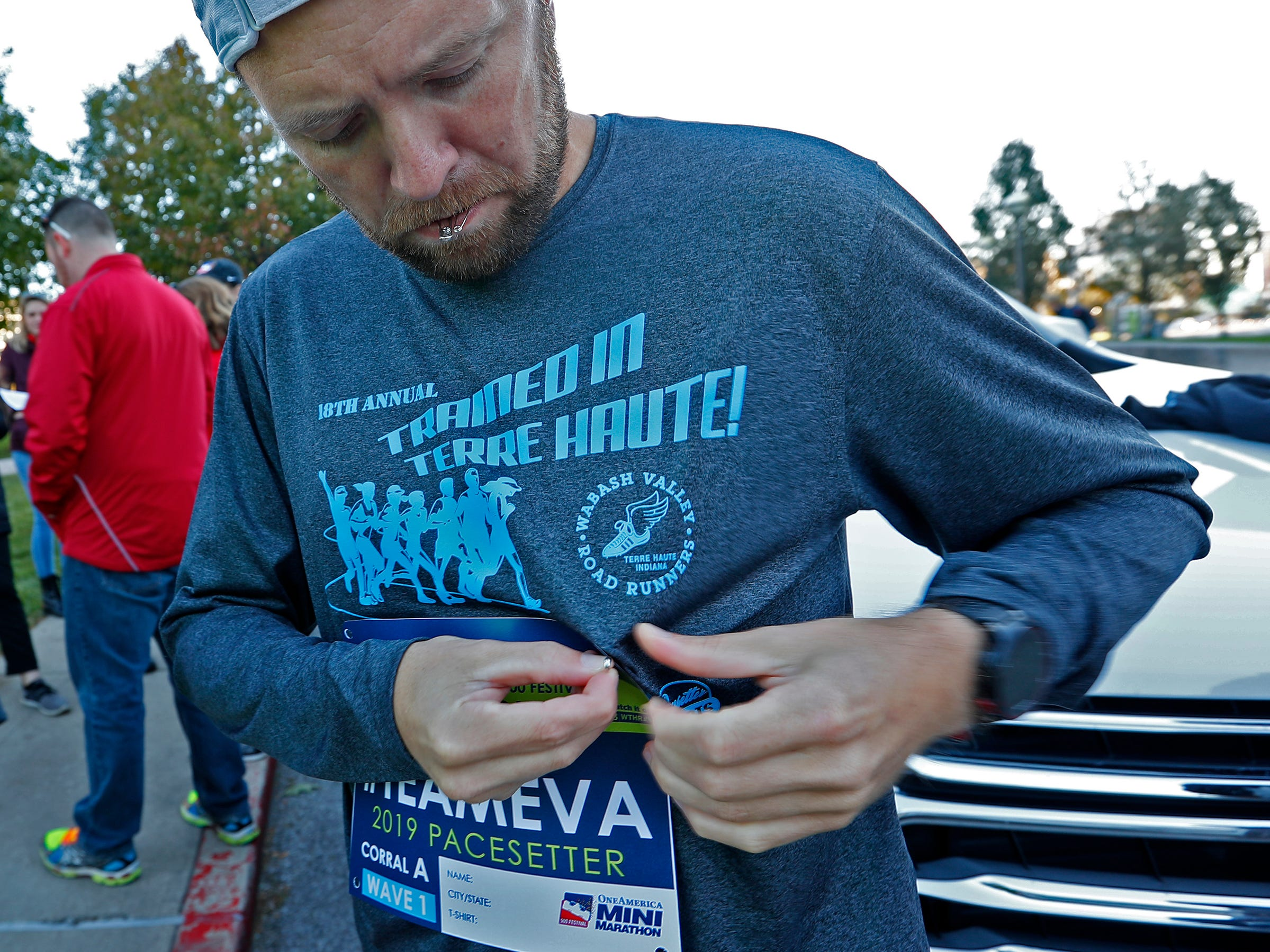 Brad Chaney puts on his Team Eva race bib before starting his leg, Wednesday, Oct. 24, 2018, of the pace-setting run for the 2019 OneAmerica 500 Festival Mini-Marathon.  The 500 Festival will donate $1 to the CANDLES Holocaust Museum in Terre Haute for every mini-marathon participant who finishes the 2019 race in a better time than Team Eva.  Holocaust survivor Eva Kor joined the fun at the Indianapolis Motor Speedway's Yard of Bricks and ran the very last part of the race.