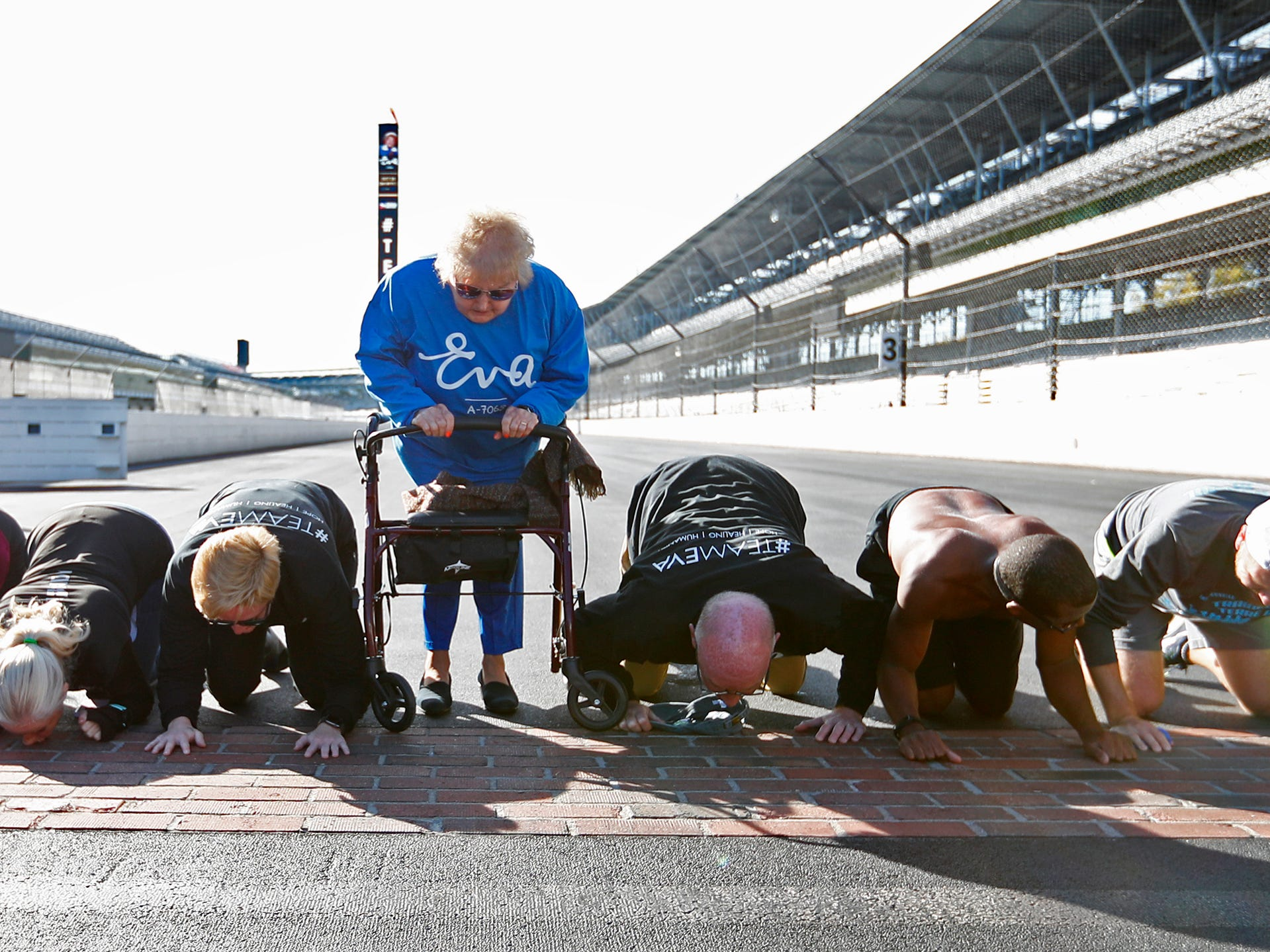 Holocaust survivor Eva Kor, center, joins others at the Indianapolis Motor Speedway Yard of Bricks for photos, Wednesday, Oct. 24, 2018, during the pace-setting run for the 2019 OneAmerica 500 Festival Mini-Marathon.  They also kissed the bricks!  The 500 Festival will donate $1 to the CANDLES Holocaust Museum in Terre Haute for every mini-marathon participant who finishes the 2019 race in a better time than Team Eva.  Kor ran the very last of the relay race.