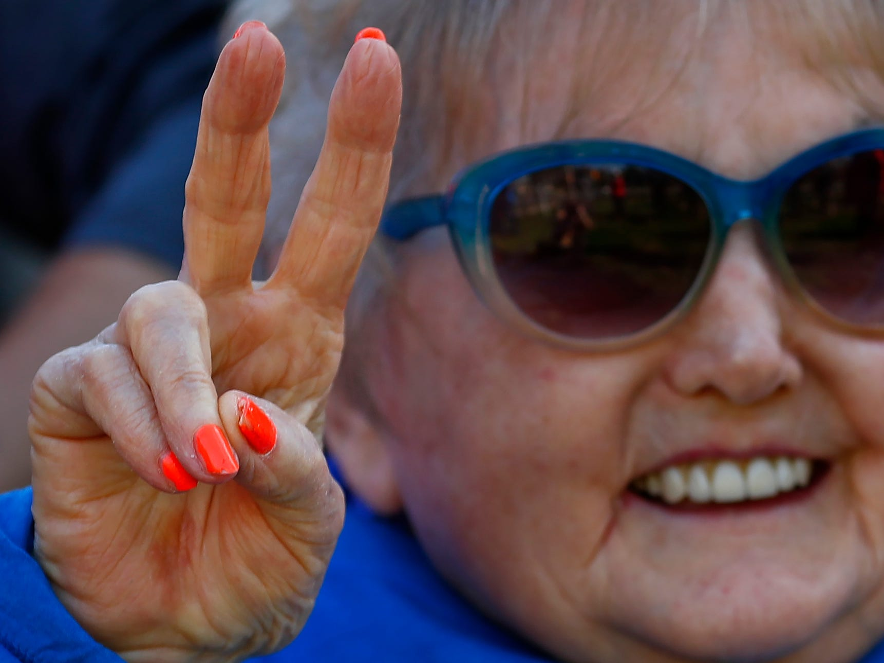 Holocaust survivor Eva Kor wears orange fingernail polish, as she smiles and joins others at the end, Wednesday, Oct. 24, 2018, of the pace-setting run for the 2019 OneAmerica 500 Festival Mini-Marathon.  The 500 Festival will donate $1 to the CANDLES Holocaust Museum in Terre Haute for every mini-marathon participant who finishes the 2019 race in a better time than Team Eva, which was 2 hours, 7 minutes, 36 seconds.  Kor ran the very last part of the relay race to add to the time.