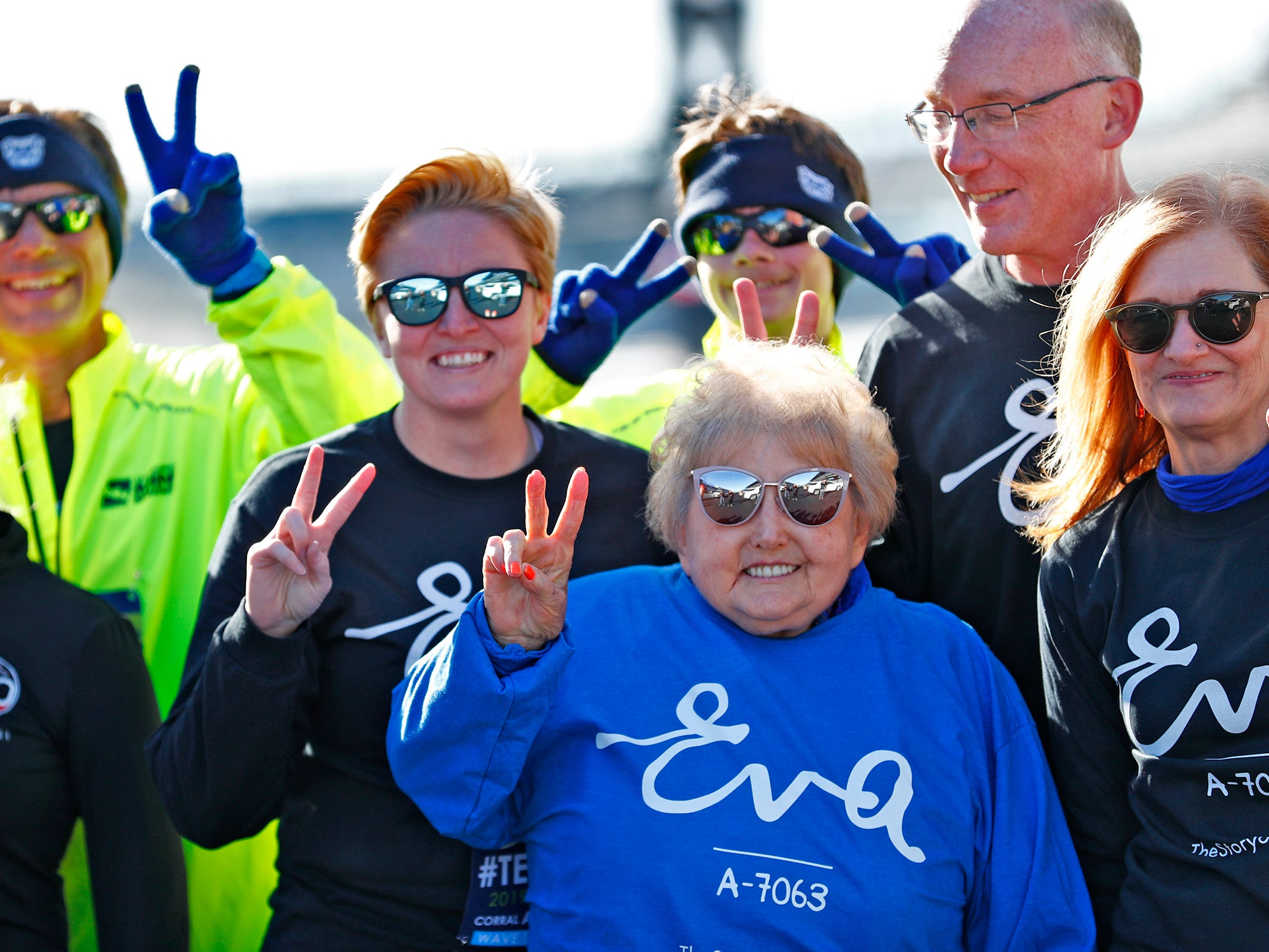 Holocaust survivor Eva Kor, center, joins others at the Indianapolis Motor Speedway Yard of Bricks for fun photos, Wednesday, Oct. 24, 2018, midway during the pace-setting run for the 2019 OneAmerica 500 Festival Mini-Marathon.  The 500 Festival will donate $1 to the CANDLES Holocaust Museum in Terre Haute for every mini-marathon participant who finishes the 2019 race in a better time than Team Eva.  Kor ran the very last of the relay race.