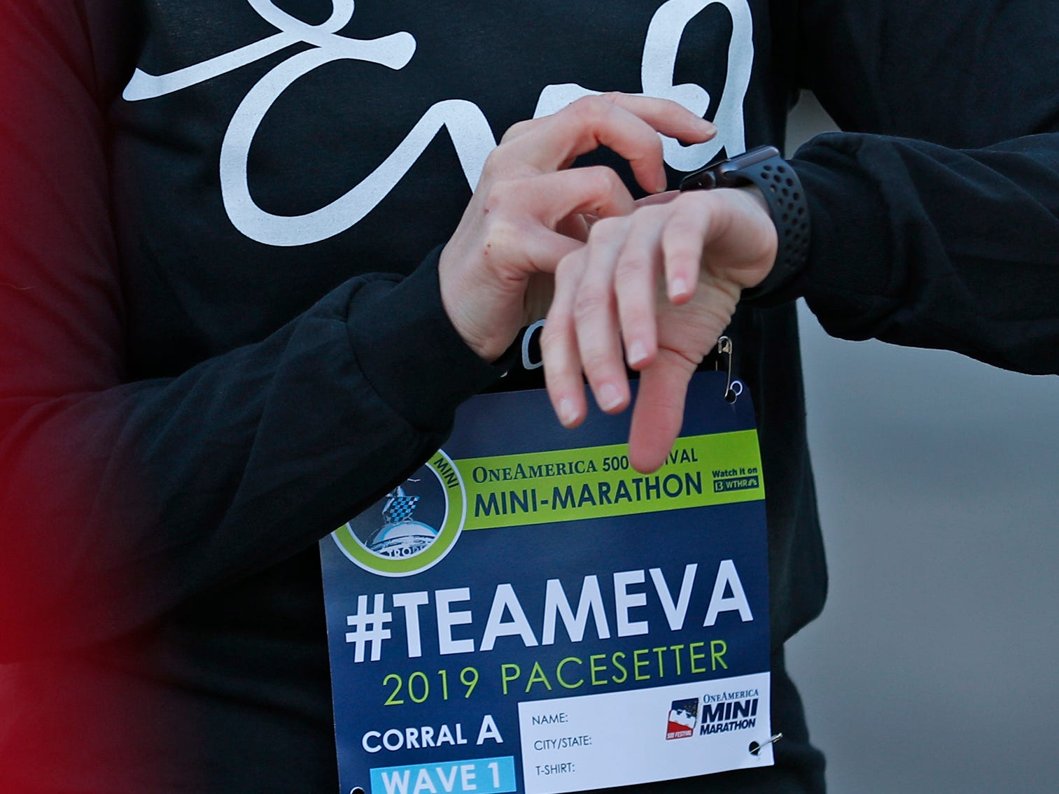 Mika Brown sets her watch before running the first leg, Wednesday, Oct. 24, 2018, of the pace-setting run for the 2019 OneAmerica 500 Festival Mini-Marathon.  The 500 Festival will donate $1 to the CANDLES Holocaust Museum in Terre Haute for every mini-marathon participant who finishes the 2019 race in a better time than Team Eva.  Holocaust survivor Eva Kor joined the fun at the Indianapolis Motor Speedway's Yard of Bricks and ran the very last part of the race.