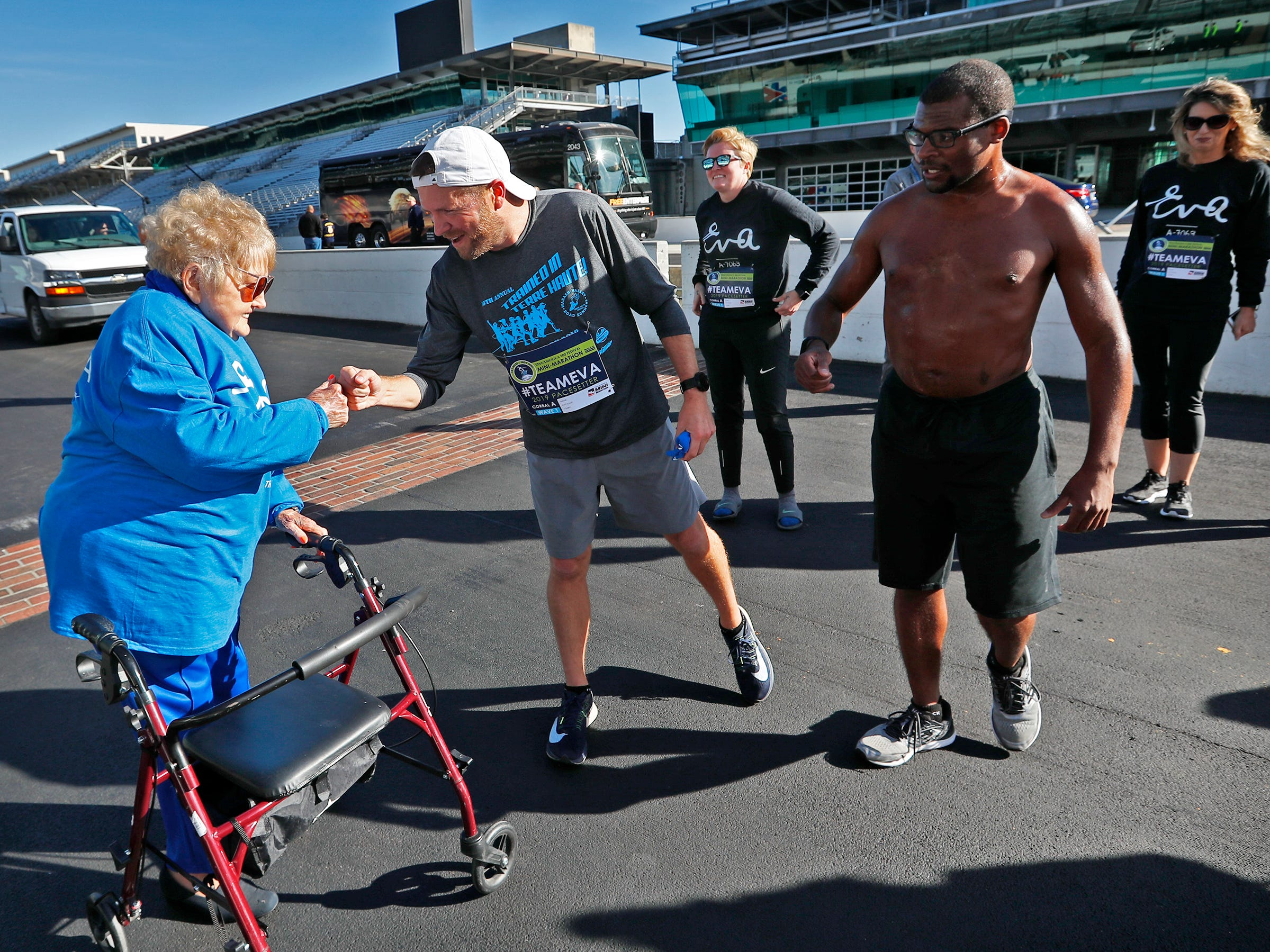 Holocaust survivor Eva Kor joins others at the Indianapolis Motor Speedway Yard of Bricks and welcomes runners, including Brad Chaney, center, and Andrew Peterson, Wednesday, Oct. 24, 2018, during the pace-setting run for the 2019 OneAmerica 500 Festival Mini-Marathon.  The 500 Festival will donate $1 to the CANDLES Holocaust Museum in Terre Haute for every mini-marathon participant who finishes the 2019 race in a better time than Team Eva.  Kor ran the very last of the relay race.