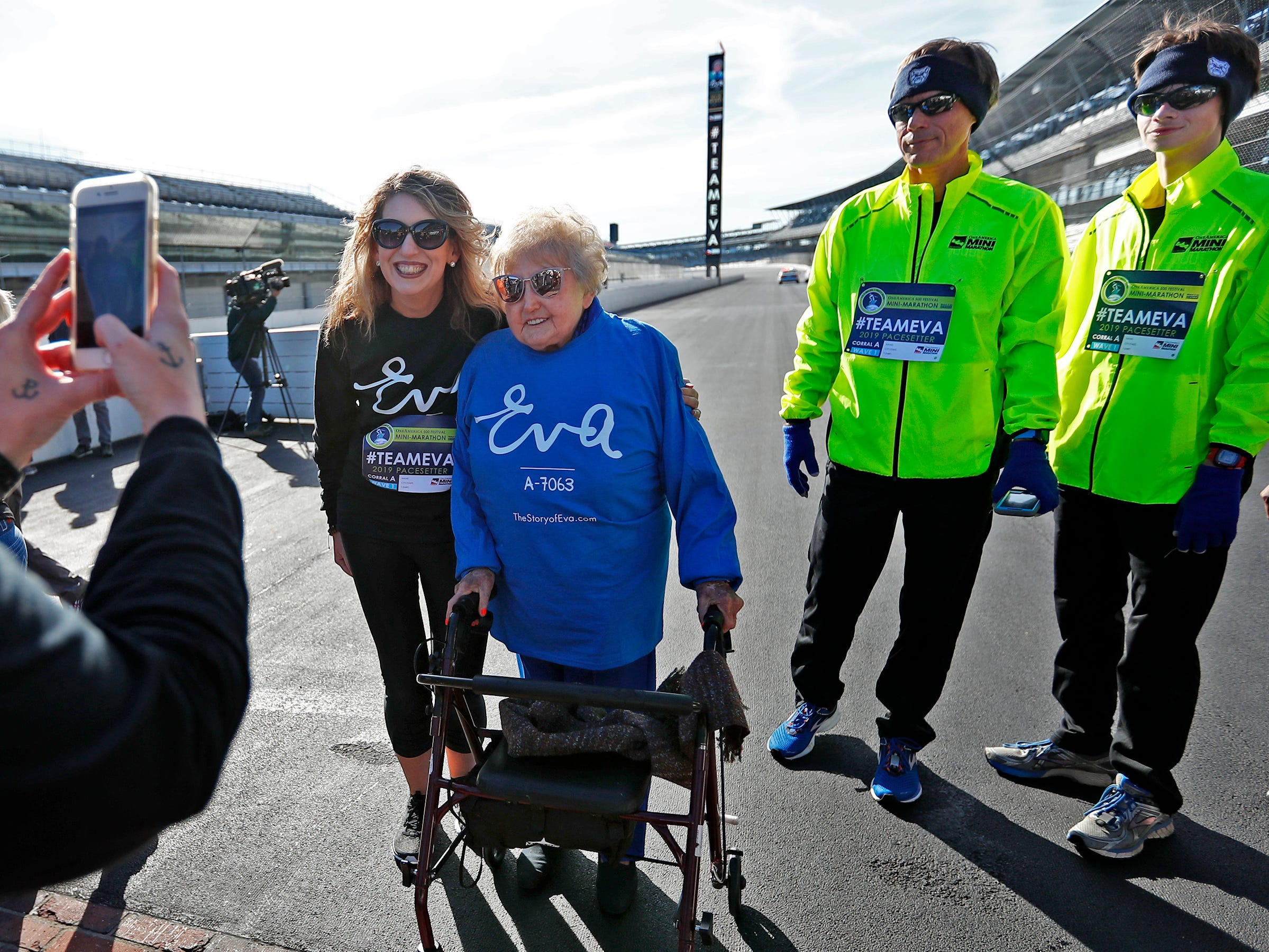 Holocaust survivor Eva Kor, center, joins others, including Epha Riche, at the Indianapolis Motor Speedway Yard of Bricks for photos, Wednesday, Oct. 24, 2018, during the pace-setting run for the 2019 OneAmerica 500 Festival Mini-Marathon.  The 500 Festival will donate $1 to the CANDLES Holocaust Museum in Terre Haute for every mini-marathon participant who finishes the 2019 race in a better time than Team Eva.  Kor ran the very last of the relay race.