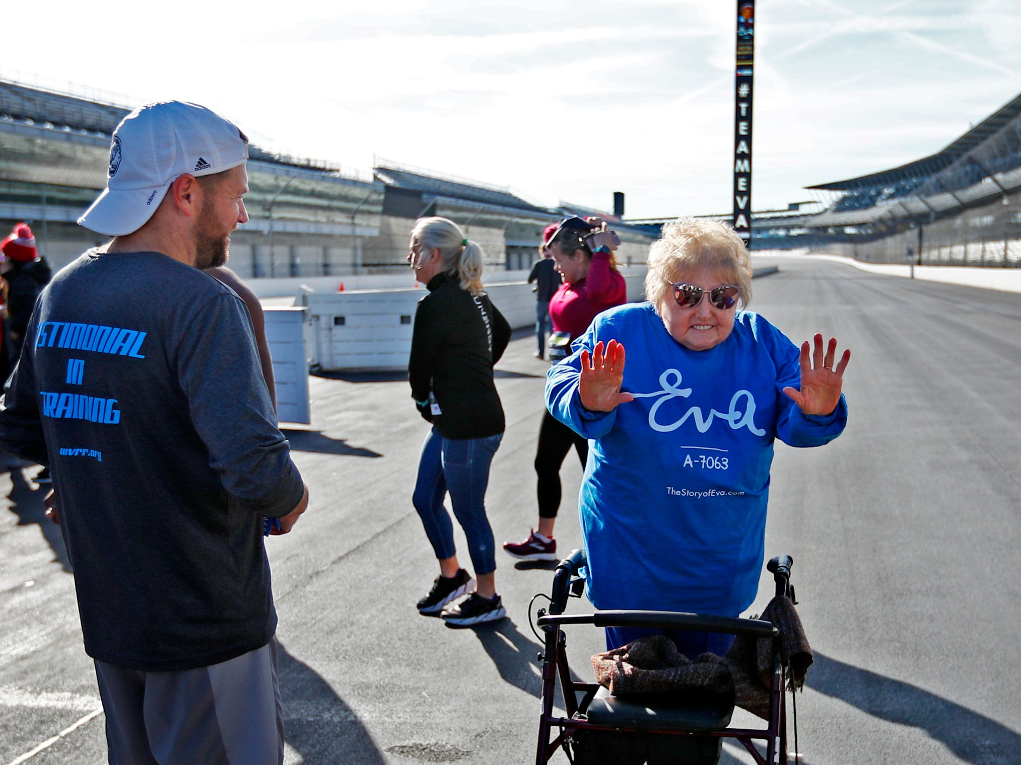Holocaust survivor Eva Kor, right, joins others and enjoys the spirit of the day, at the Indianapolis Motor Speedway Yard of Bricks, Wednesday, Oct. 24, 2018, midway during the pace-setting run for the 2019 OneAmerica 500 Festival Mini-Marathon.  The 500 Festival will donate $1 to the CANDLES Holocaust Museum in Terre Haute for every mini-marathon participant who finishes the 2019 race in a better time than Team Eva.  Kor ran the very last of the relay race.