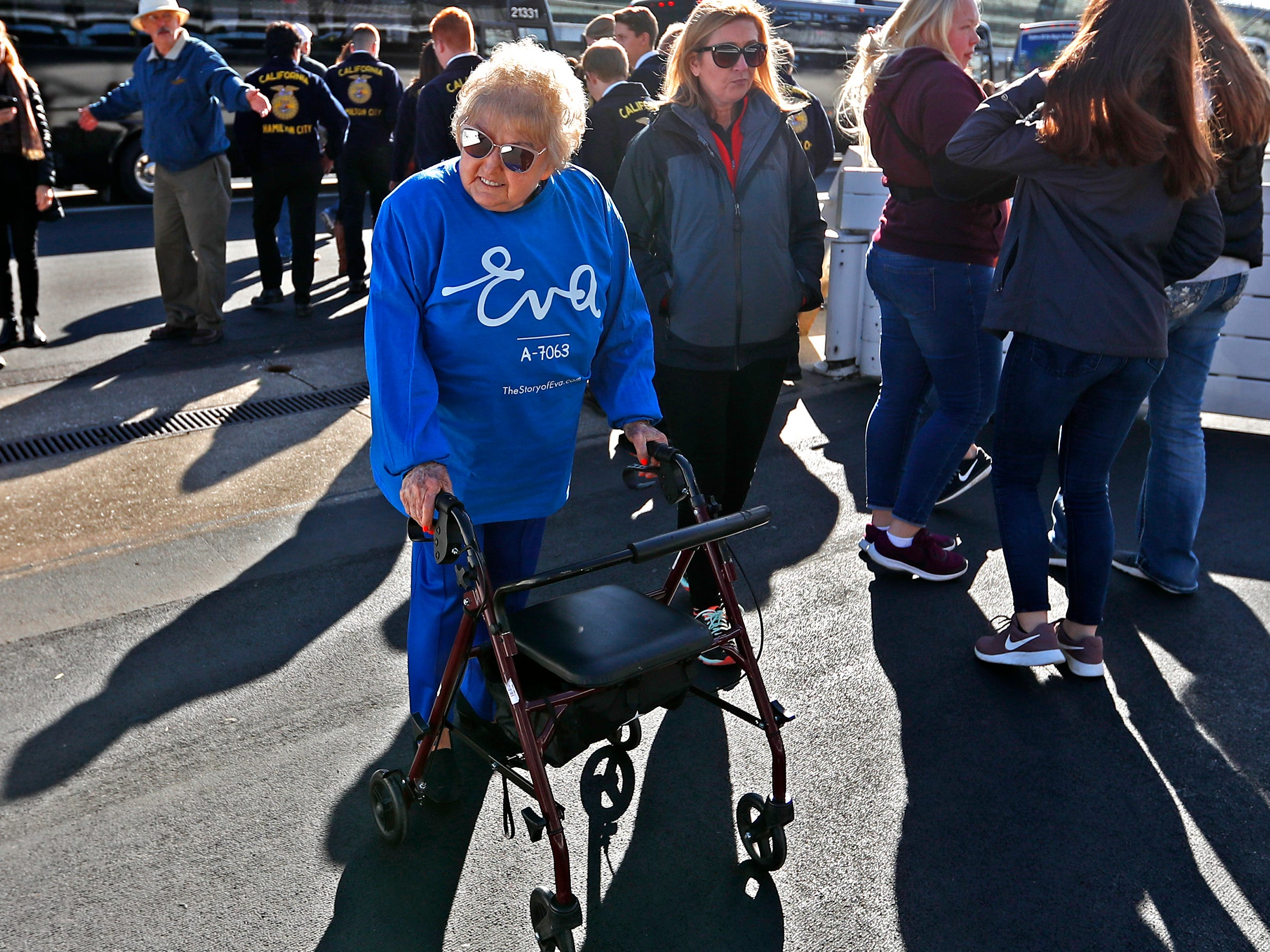 Holocaust survivor Eva Kor joins others at the Indianapolis Motor Speedway Yard of Bricks to get ready to welcome runners and pose for photos, Wednesday, Oct. 24, 2018, during the pace-setting run for the 2019 OneAmerica 500 Festival Mini-Marathon.  The 500 Festival will donate $1 to the CANDLES Holocaust Museum in Terre Haute for every mini-marathon participant who finishes the 2019 race in a better time than Team Eva.  Kor ran the very last of the relay race.