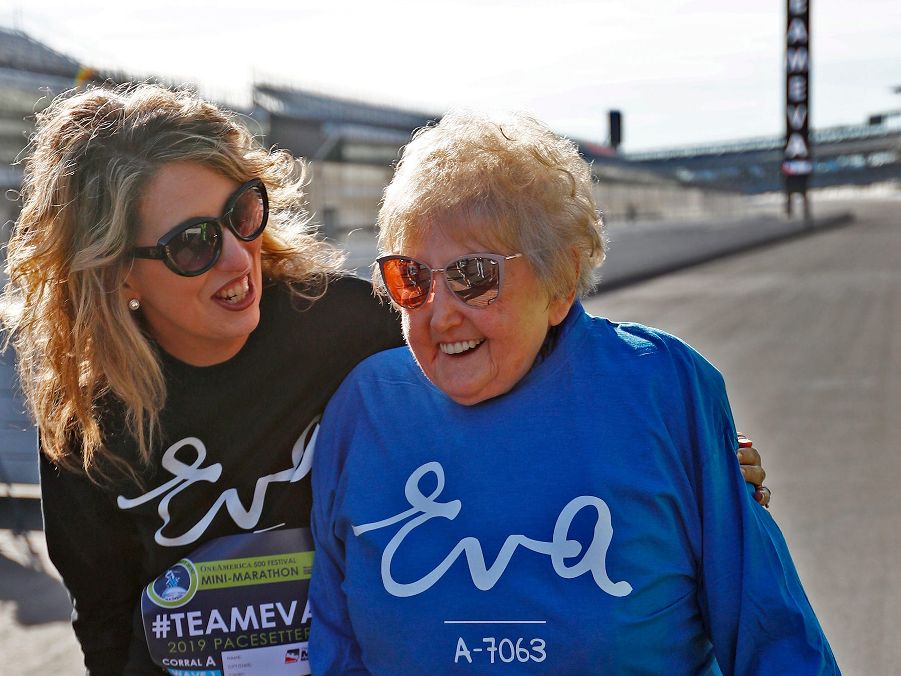 Holocaust survivor Eva Kor, right, joins others, including Epha Riche, at the Indianapolis Motor Speedway Yard of Bricks for photos, Wednesday, Oct. 24, 2018, during the pace-setting run for the 2019 OneAmerica 500 Festival Mini-Marathon.  The 500 Festival will donate $1 to the CANDLES Holocaust Museum in Terre Haute for every mini-marathon participant who finishes the 2019 race in a better time than Team Eva.  Kor ran the very last of the relay race.