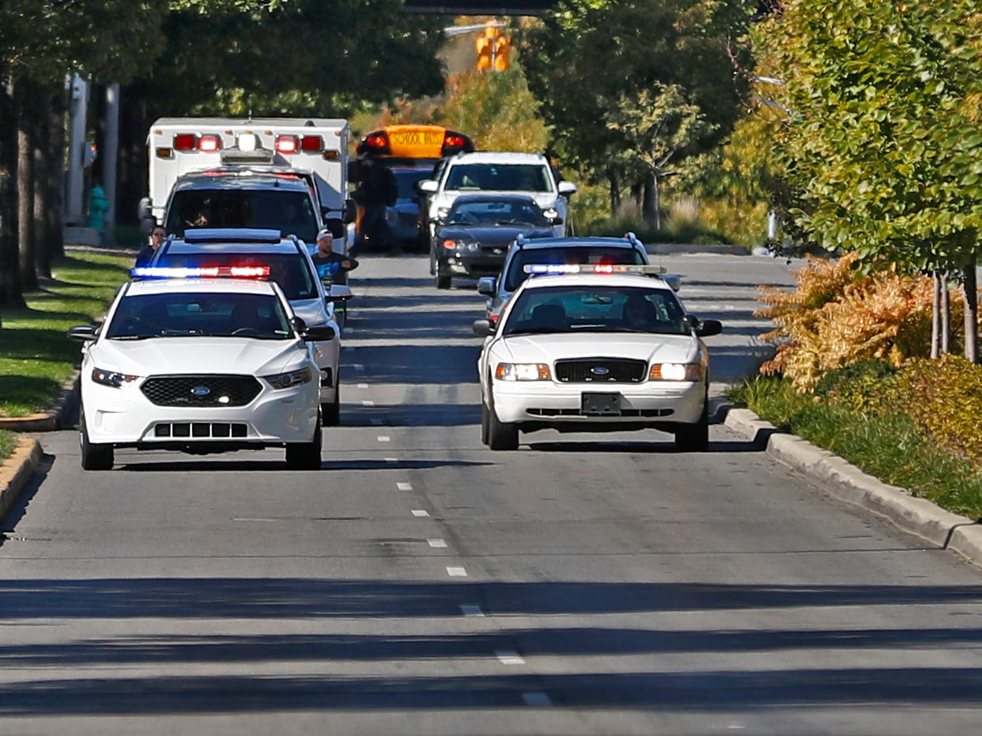A police escort brings the last leg of the running relay down New York St., Wednesday, Oct. 24, 2018, to finish the pace-setting run for the 2019 OneAmerica 500 Festival Mini-Marathon.  The 500 Festival will donate $1 to the CANDLES Holocaust Museum in Terre Haute for every mini-marathon participant who finishes the 2019 race in a better time than Team Eva.  Holocaust survivor Eva Kor ran the very last leg of the relay race.