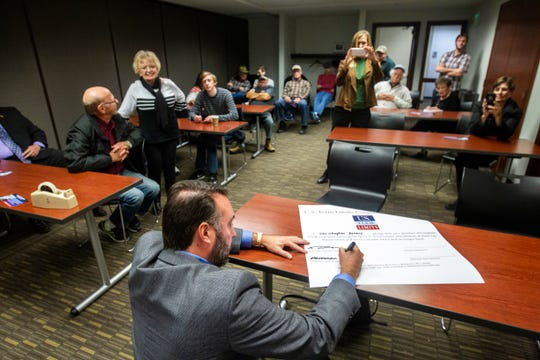 Christopher Peters, Republican second congressional district candidate, signs a pledge after a U.S. Term Limits event on Thursday, Oct. 18, 2018, at Public Library in Coralville.