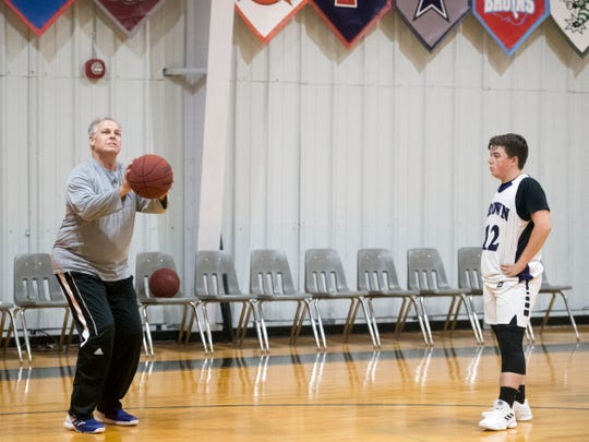 """Crown College basketball coach Clayton Sullivan demonstrates a drill to Tyler Antman during practice on Tuesday, October 23, 2018. """"The pace of the college game is so much faster than anything I knew in high school,"""" said Sullivan. """"It was an adjustment for me."""""""