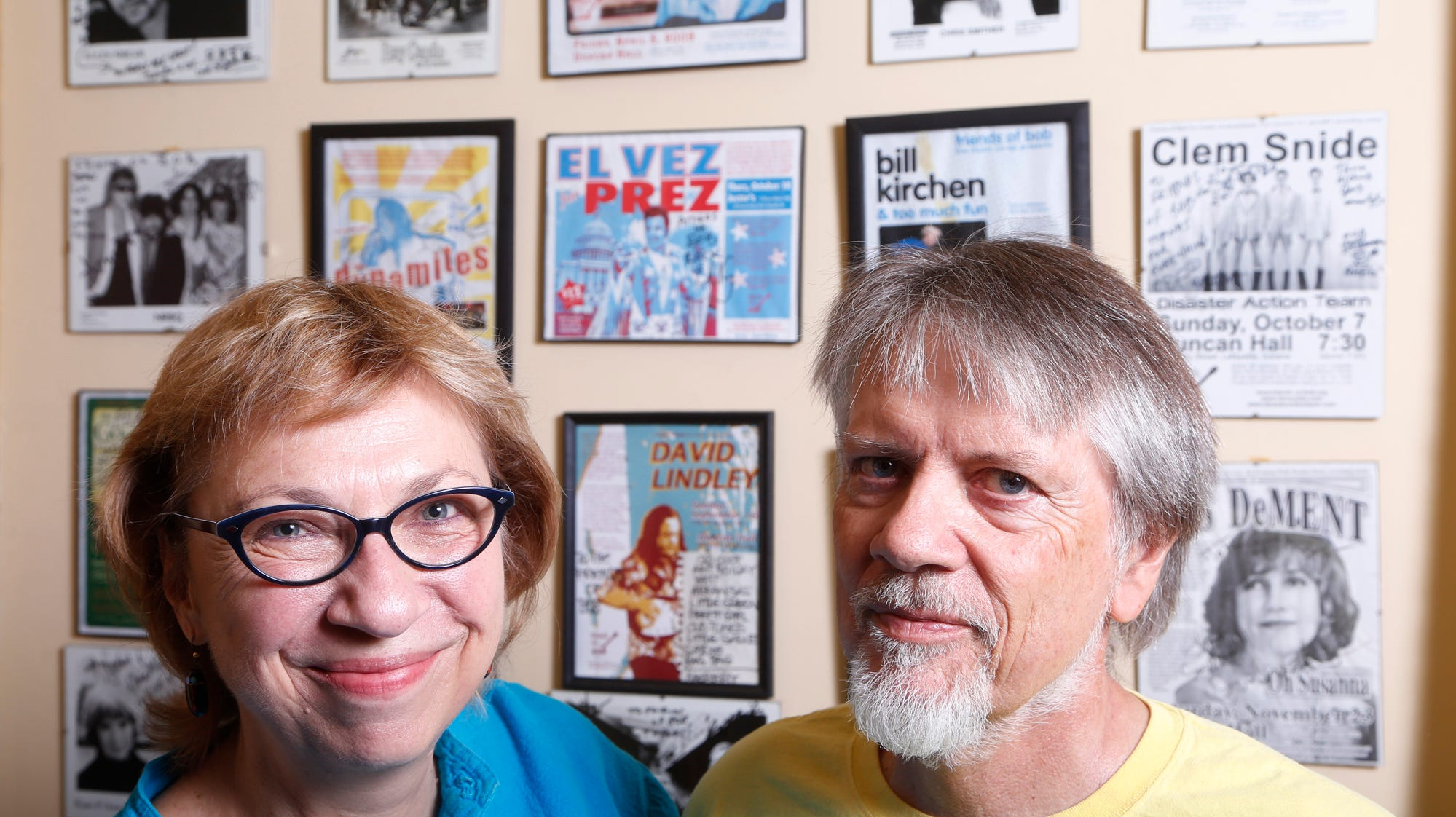 Richard Fudge and Meredith Richmond stand next to a wall decorated with promotional photos from musicians featured in Friends of Bob shows Wednesday, October 24, 2018, in their Battle Ground home. The popular Friends of Bob performances will come to an end after 25 years and 187 memorable shows.