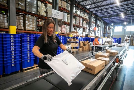 Radial employee Valerie Mathies makes sure packages are properly aligned on a conveyer belt before being shipped from the fulfillment center off Trade Port Drive in Louisville's South End recently. Oct. 24, 2018