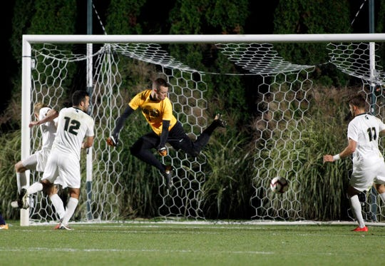Michigan State goalkeeper Jimmy Hague makes a save as John Freitag (12) and Ryan Sierakowski (11) also defend against Michigan, Tuesday, Oct. 23, 2018, in East Lansing, Mich. The teams played to a 1-1 draw.