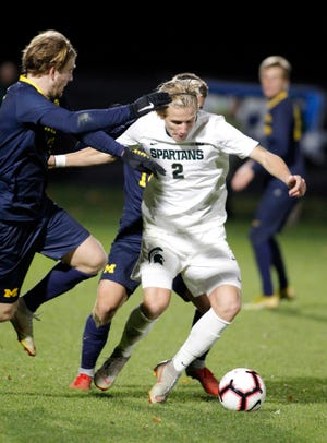 Michigan State's Jack Beck (2) works against Michigan's Jack Hallahan, left, and Robbie Mertz, rear, Tuesday, Oct. 23, 2018, in East Lansing, Mich. The teams played to a 1-1 draw.