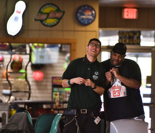 Tony Kujawa, 34, of Grand Ledge,  left, and Michael Sims, an employee of Community Mental Health react after Kujawa got a strike during practice, Monday, Oct. 22, 2018, at Char-Lanes in Charlotte.  Kujawa bowled a perfect game there Oct. 15, 2018.