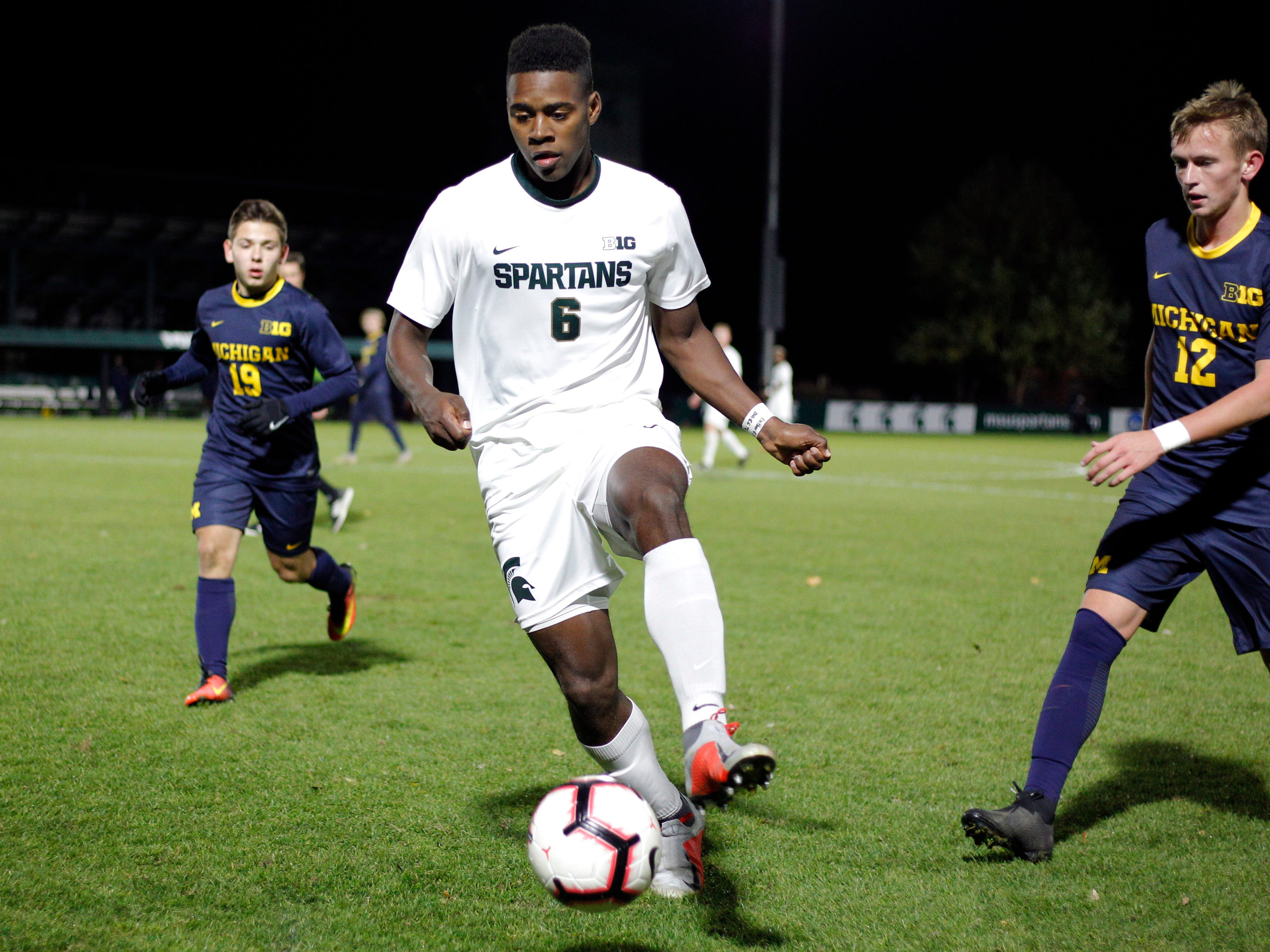 Michigan State's DeJuan Jones (6) controls the ball against Michigan's Kevin Buca, left, and Austin Swiech, right,, Tuesday, Oct. 23, 2018, in East Lansing, Mich. The teams played to a 1-1 draw.