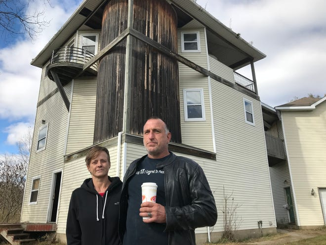 """Michelle and Scott Maurer on Wednesday, Oct. 24, 2018 in front of the abandoned, four-story """"highway house"""" on Billwood Highway in Dimondale they've purchased. They aim to restore it and make a home there."""