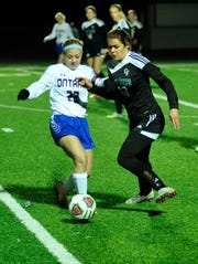 Ontario's Bria Meisse kicks the ball away from Clear Fork's Bianca Hoffer in the district semifinal match.