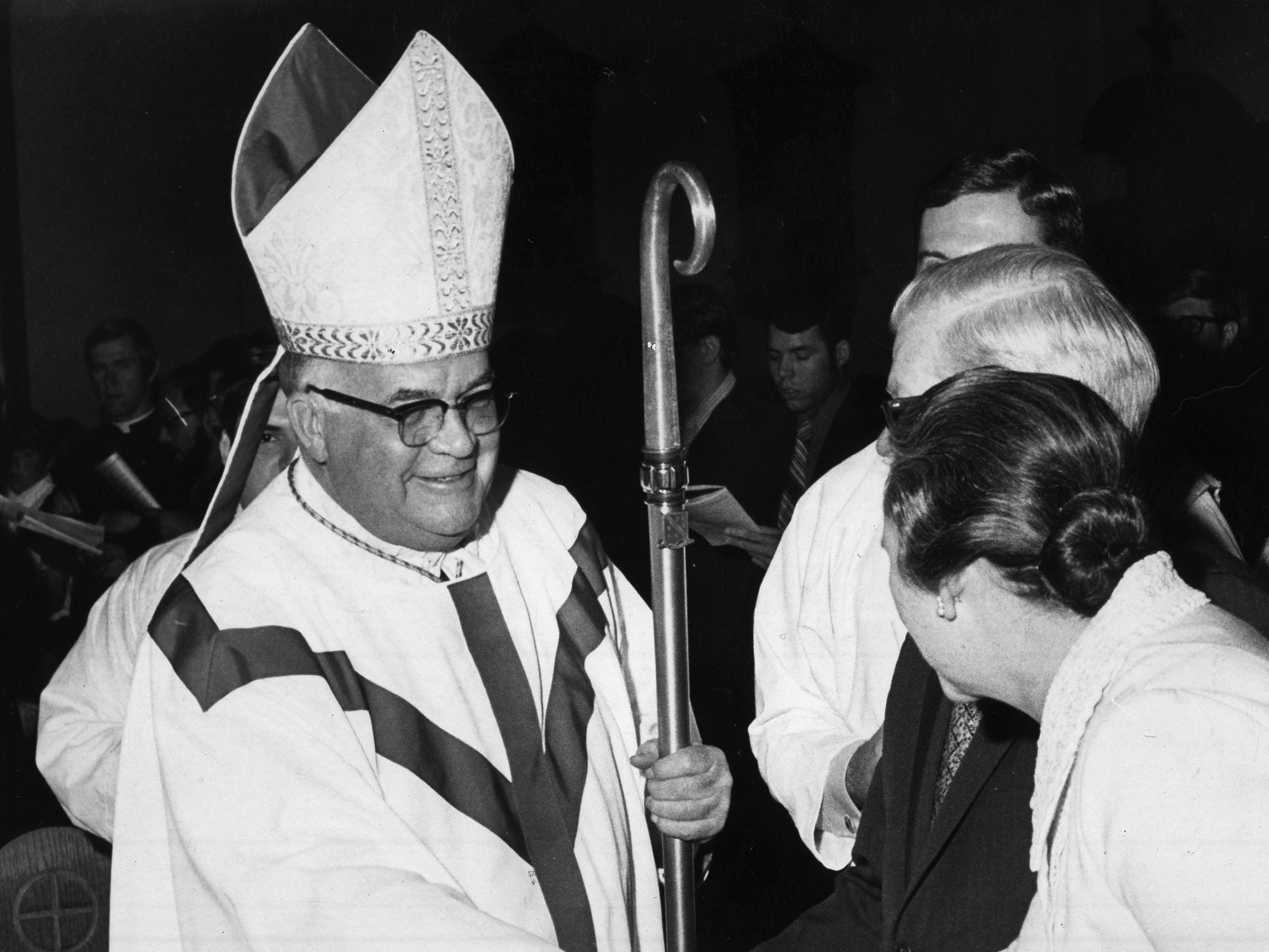 Bishop Carroll T. Dozier, of the Catholic Diocese of Memphis, shakes hands with Dr. and Mrs. David Taylor during a processional on May 21, 1971.