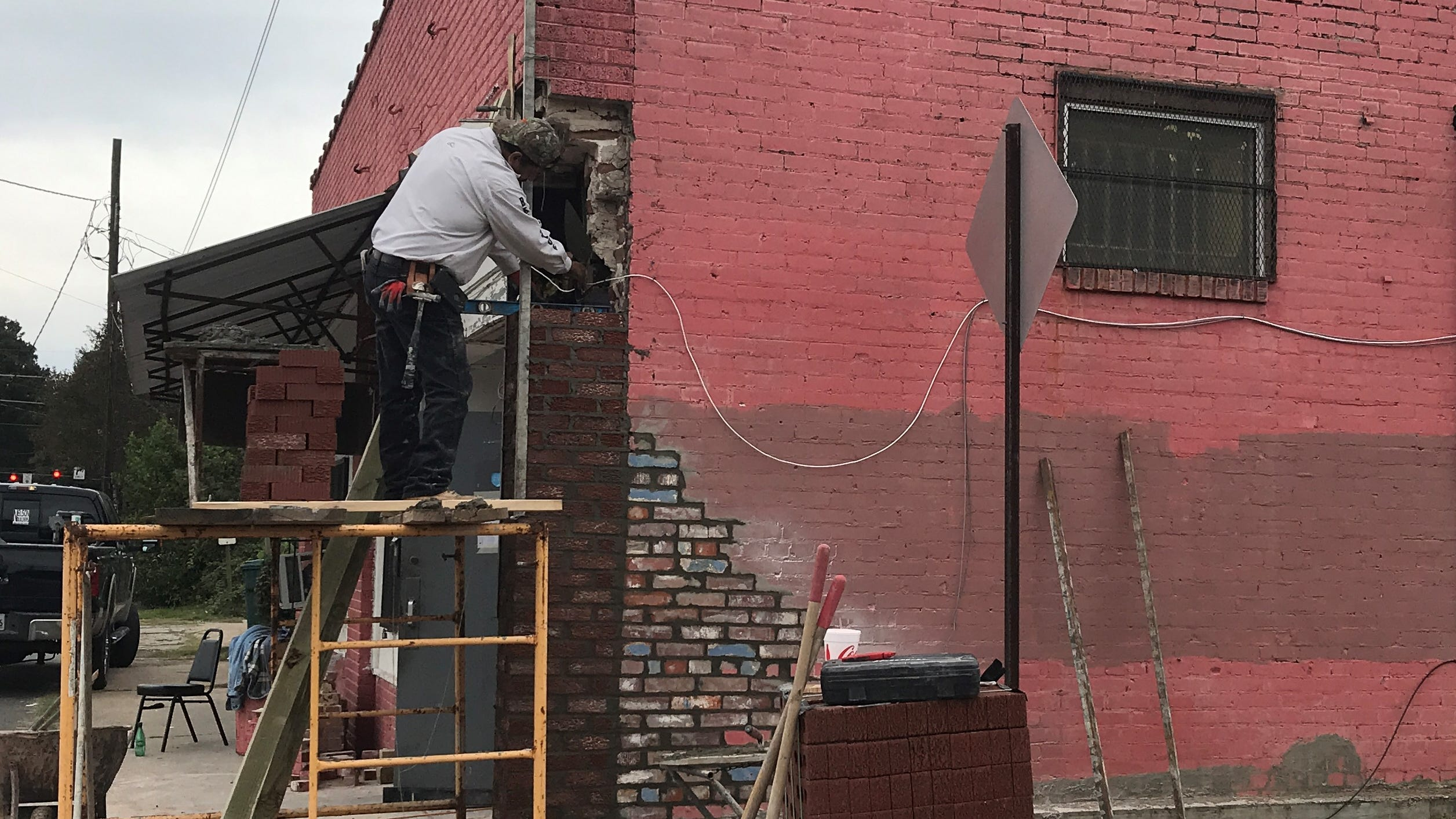 Carlos Robles of Robles Builders repairs the wall at the Community Soup Kitchen in Monroe on Tuesday.
