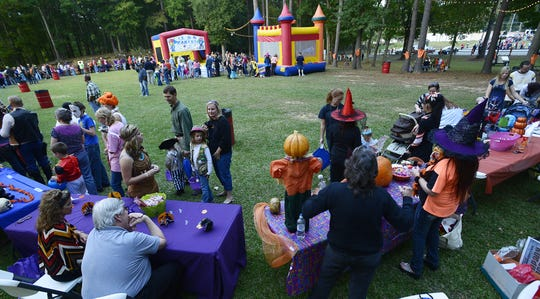 Trick or treaters make their way past tables receiving candy at the city of Wetumpka Candy Walk