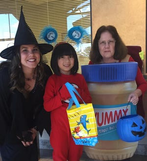 Town of Pike Road receptionist Sandra Mullins (PB&J), and assistant to the town clerk Tosha Darnell (friendly witch), smile with local children who trick-or-treated at Town Hall-oween in 2017.