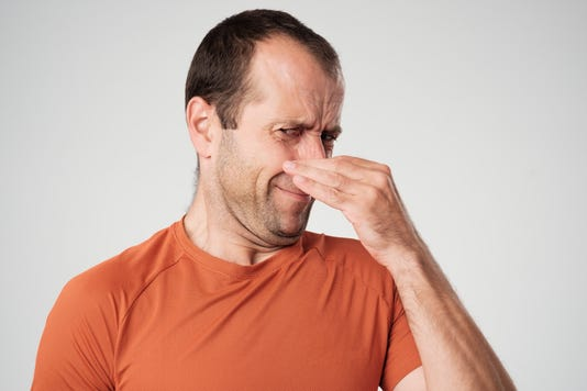 Caucasian Man Is Pinching Nose With Fingers And Looking With Disgust Because Of Bad Smell Isolated On White Background