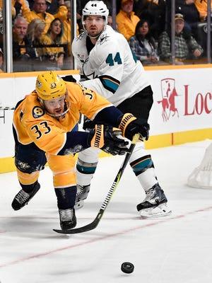 Predators right wing Viktor Arvidsson (33) slaps the puck away from Sharks defenseman Marc-Edouard Vlasic (44) during the first period at Bridgestone Arena Tuesday, Oct. 23, 2018, in Nashville, Tenn.