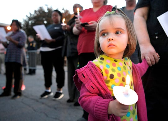 Bray Kelley, 4, holds a candle on the Columbia public square during a prayer vigil on Tuesday.