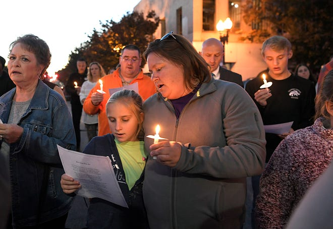 People pray and sing on the Columbia public square during a community vigil on Tuesday, Oct. 23, 2018 for the victims and surviving members of an apparent murder-suicide involving a Columbia mother and four of her children.