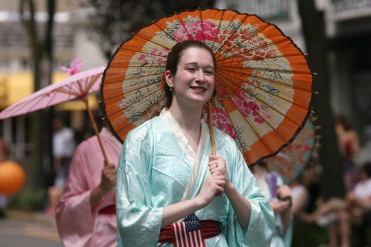 """Members of the Ridgewood Gilbert and Sullivan Opera march in The Ridgewood Fourth of July Parade in 2013 in costume for  the """"Mikado""""."""