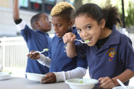 Third-grader, Savant Diaz, eats salad, just outside the Mobile Food Lab in Garfield. Tuesday, October 23, 2018