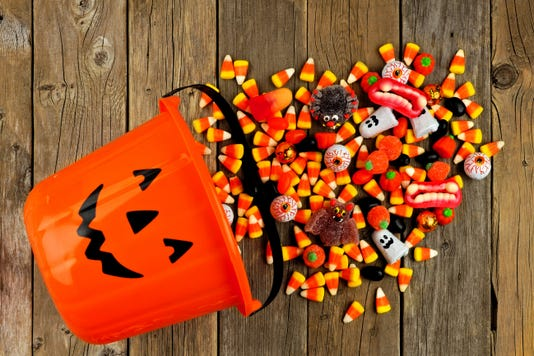 Halloween Jack O Lantern Pail With Spilling Candy Over Wood