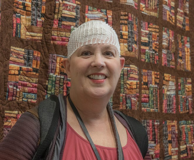 Rebecca Havenstein-Coughlin is retiring after 38 years at the Canton Public Library. Behind her is a book-themed quilt, presented to her by her co-workers.
