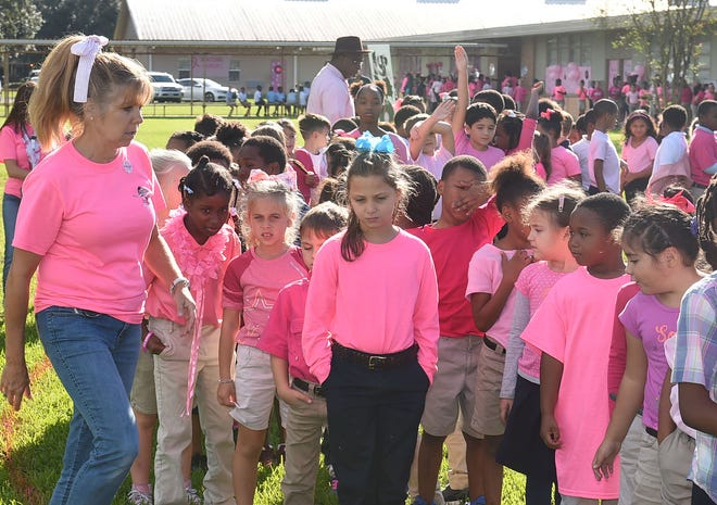 Park Vista Elementary students prepare to create a human pink ribbon in observance of National Breast Cancer Awareness Month.