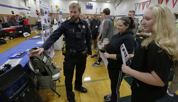 Winnebago County Sheriff's Deputy Ryan Hathaway talks with Callie Schwerin and Hailey Redman during the Oshkosh Chamber of Commerce's Career Exploration Fair on Tuesday, Oct. 23, 2018, at Oshkosh West High School. About 1,000 students from Oshkosh and Omro middle and high schools participated in this year's expanded fair, thanks to a $5,000 grant from AT&T.
